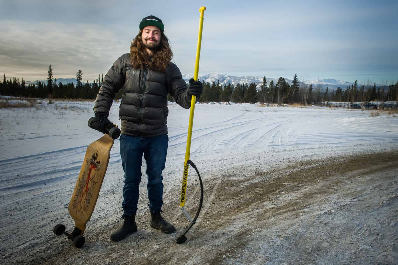 CCI client posing with his invention, a skateboard stick
