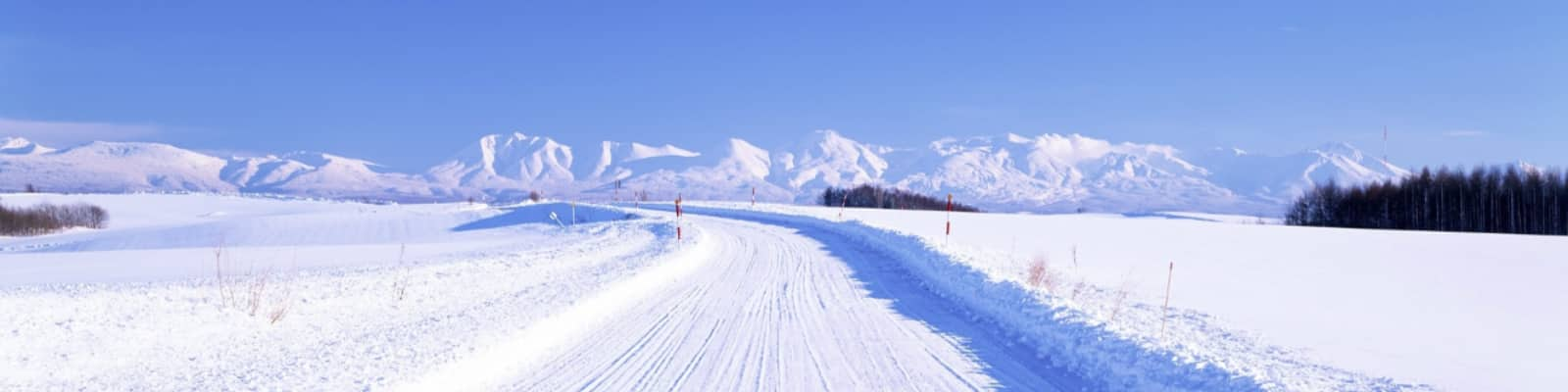 A snow covered road and a vivid blue sky