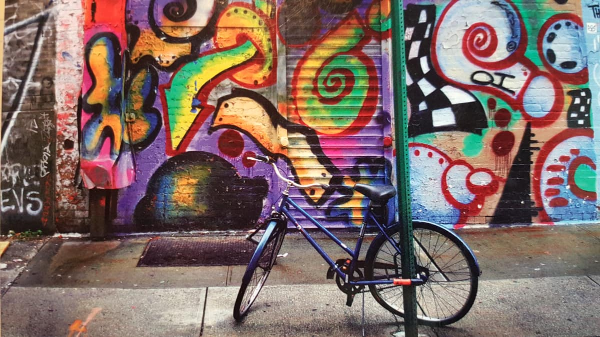 bike parked in front of wall with graffitti