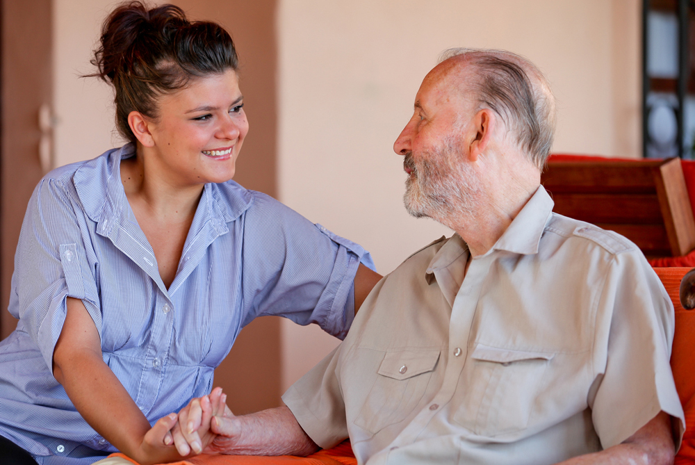 Health Care Assistant engaged in conversation with elderly man