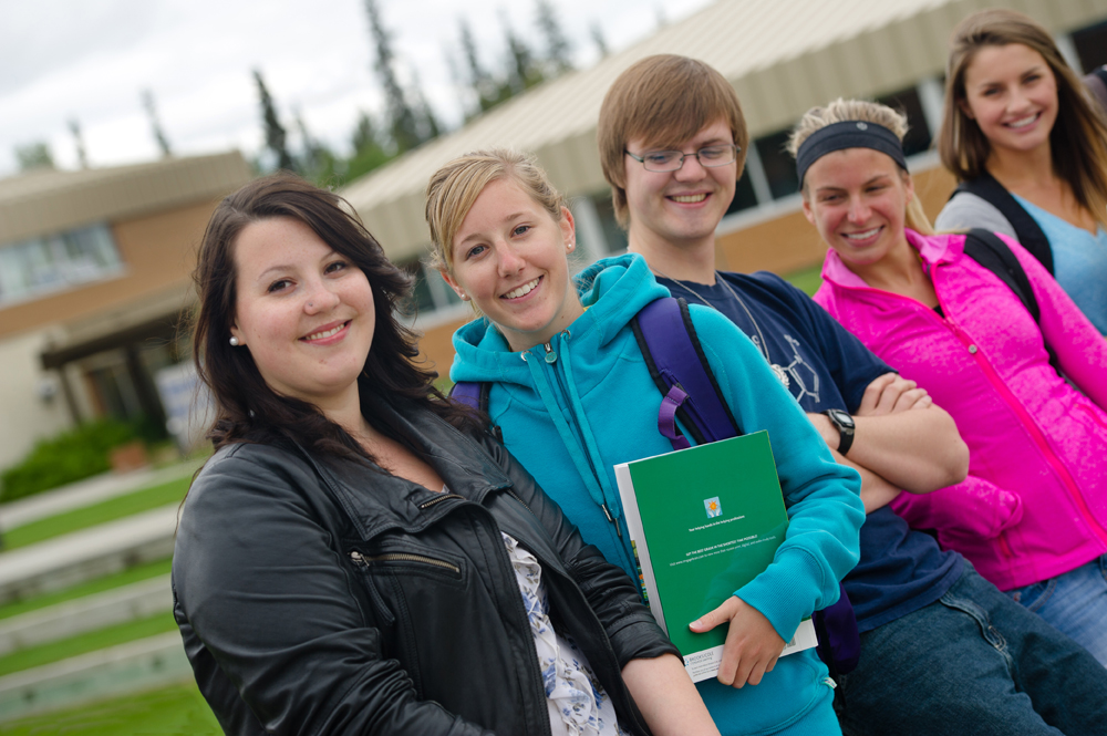 smiling students outside Ayamdigut Campus, Whitehorse
