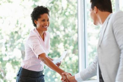 A woman and man shake hands in a business setting