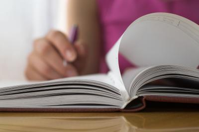 A person flipping pages in a book with pen in hand