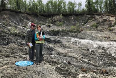 Two people operating a drone at a permafrost slump