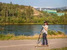 Joel Brennan rides a longboard along the waterfront trail using the SUPStick he invented